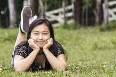 Cute asian girl smiling lying on the grass on the grass on blurred woods background Stock Photo