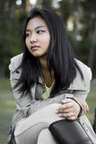 Cute sad asian girl with a coat on blurred woods background Stock Photo