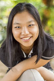 Cute happy asian girl on blurred woods background Royalty Free Stock Images