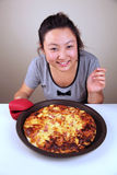 Cute Asian girl holding a pizza Royalty Free Stock Image