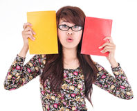 Cute asian girl holding two books, red and yellow colors Stock Photography