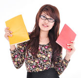 Cute asian girl holding two books, red and yellow colors Royalty Free Stock Photography