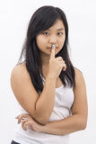 Cute serious asian girl on isolated background thinking making silence sign Stock Images