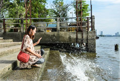 A cute Asian girl kneeling near the riverside dock Stock Image