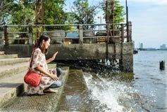 A cute Asian girl kneeling near the riverside dock Stock Image