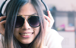 Cute Asian girl is listening to pop dance music. On headphone Royalty Free Stock Image