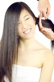 Cute asian girl with long hair getting combed by stylist Royalty Free Stock Photos