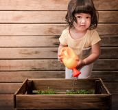 Cute Asian Girl Looking at Camera while Enjoying with Gardening Stock Images