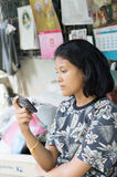 Cute Asian girl looking at mobile phone Stock Photography