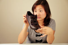 Cute Asian girl looking at a shoe Royalty Free Stock Photo