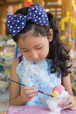 Cute asian girl painting color on the plaster statue. A cute asian girl painting color on the plaster statue Stock Photography
