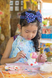Cute asian girl painting color on the plaster statue. Royalty Free Stock Images