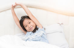 Cute asian girl in pajamas is sitting on  bed stretching. Royalty Free Stock Photo