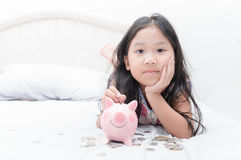 Cute asian girl putting coin to piggy bank on bed. Stock Photography