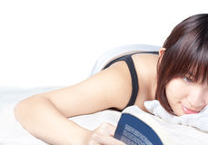 Cute Asian girl reading on bed Royalty Free Stock Photography