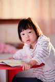 Cute Asian girl reading a book with nature light. Royalty Free Stock Images