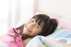 Cute Asian girl relaxing on bed at home Stock Photos