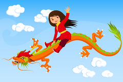 Cute Asian girl riding a dragon. Against blue sky Royalty Free Stock Photography
