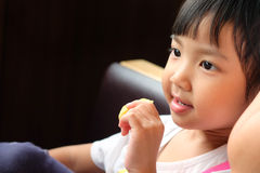 Cute Asian girl sitting eating happily. stock image