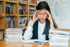 Cute Asian girl sitting in a library, surrounded by books, thinking about studying. Headache, migraine, stress after study. Teen stock photo