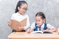 Cute asian girl student in uniform writing her homework Stock Photos