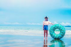 Cute asian girl on summer sea beach holding swim ring, wearing hat, eyeglasses and smiling with happiness, people on summer. Holiday vacation stock image