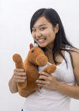 Cute asian girl smiling with a teddy horse royalty free stock photography
