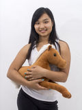 Cute smiling asian girl with a teddy horse Stock Photo