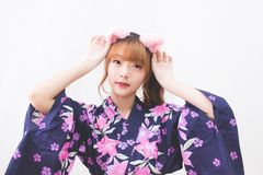 Cute Asian girl Thai people wearing yukata dress, lifted her face and grabbed the headband of a cat`s ear. Cute Asian girl Thai people wearing yukata dress stock photos