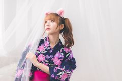 Cute Asian girl Thai people wearing yukata dress, lifted her face and grabbed the nets. In the white bedroom in the daytime. Cute Asian girl Thai people wearing royalty free stock images
