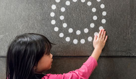 Cute Asian girl using hands with white dot graphic and circle di Stock Photography