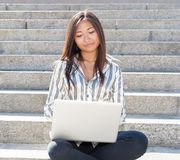 Cute asian girl using a laptop outdoor Royalty Free Stock Photography