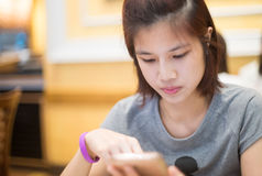Cute Asian girl is using a mobile phone Stock Image