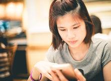 Cute Asian girl is using a mobile phone Royalty Free Stock Photos