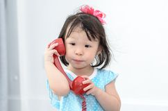 Asian girl using red vintage phone at home. Stock Image