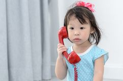 Asian girl using red vintage phone at home. Royalty Free Stock Image