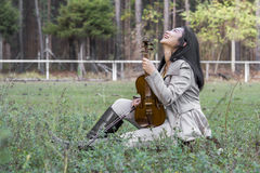 Cute asian girl with a violin on the grass on blurred woods background Royalty Free Stock Photo