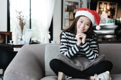 Cute asian girl wearing Christmas hat with smiling face sitting. On sofa, Merry Christmas and happy new year concept Royalty Free Stock Images