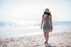 Asian girl on the beach. Cute Asian girl in white dress walking on the beach thailand alone attractive beautiful blue coast day female happy hat holiday lady royalty free stock images