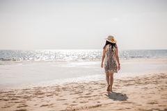 Asian girl on the beach. Cute Asian girl in white dress walking on the beach thailand alone attractive beautiful blue coast day female happy hat holiday lady royalty free stock image