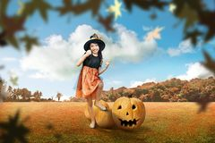 Cute asian girl in witch costume standing with scary pumpkin royalty free stock photography