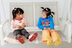 Cute Asian Girls. Two cute Asian girls sitting on a white swing stock image