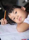 Cute asian girls is doing her homework. Royalty Free Stock Photos