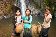 Cute Asian girls near tropical waterfall. Vang Vieng, Laos. VANG VIENG, LAOS - 15 DEC, 2013: Unidentified cute Asian girls with baskets washing vegetables in Stock Photography