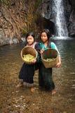 Cute Asian girls near tropical waterfall. Vang Vieng, Laos. VANG VIENG, LAOS - 15 DEC, 2013: Unidentified cute Asian girls with baskets washing vegetables in royalty free stock photos
