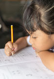 Cute asian girls is very determined her homework. Royalty Free Stock Images
