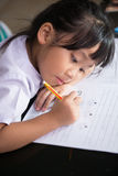 Cute asian girls is very determined her homework. Stock Image