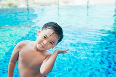 Cute asian kid cleaning ears after swimming in a pool Royalty Free Stock Photo