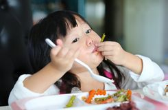 Cute asian kid girl age about 2 years old eating rice by self.  royalty free stock photos
