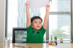 Cute asian kid sit at the table with colorful folders and draws with pen, hold paper painting royalty free stock photos